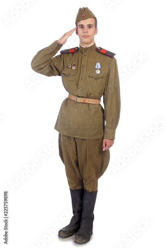 Fotografia  A soldier in military uniform of soviet army stay straight and salute