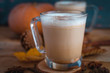 Close-up of pumpkin spice latte in glass cups, on wooden background