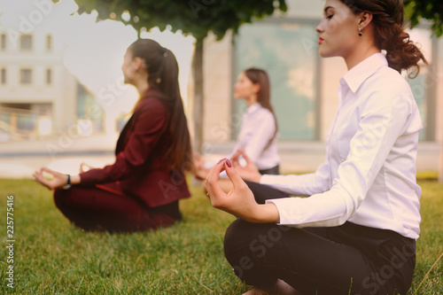 Three young girls dressed in office clothes are practicing yoga on the grass