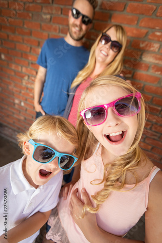 фотография Cute Young Caucasian Brother And Sister Wearing Sunglasses with Parents Behind