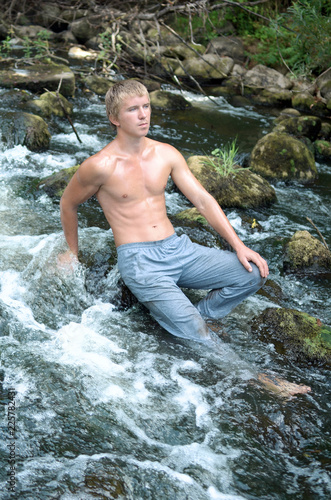 Deurstickers Akt young man resting in nature, swimming in the Northern river