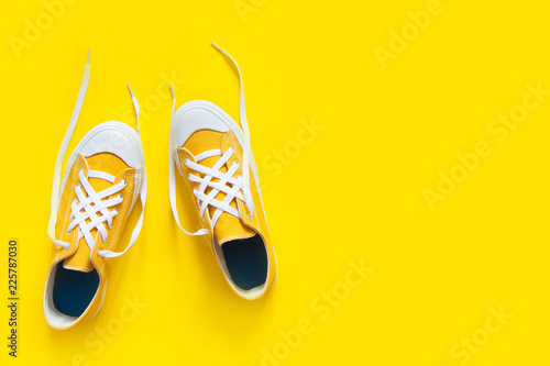Fotografia Short low  bright sneakers on a yellow background.