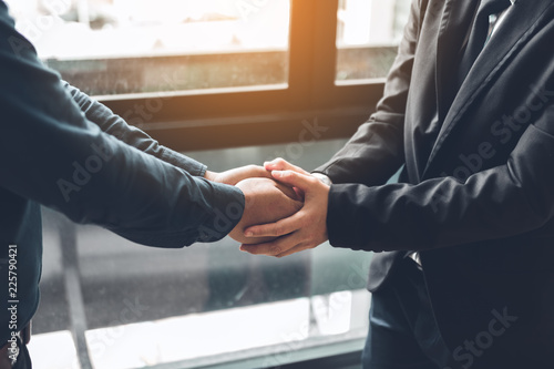 Stampa su Tela  Business people compassionately holding hands at office room.