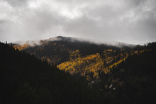 Clouds Hanging Low Over Mountains Covered In Aspens During Autumn.