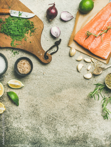 Cooking salted salmon fish. Flat-lay of raw salmon fillet, variety of salts and herbs over grey concrete table background, top view, copy space, vertical composition. Slow or comfort food concept