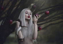 Eve With The Serpent The Tempter And The Apple Of Sin. Young Beautiful Nude Girl With Very Long White Hair With A Snake Under The Apple Tree.
