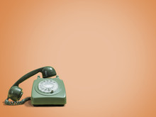 Vintage Green Rotary Phone With Headset Removed On A Retro Orange Background With Space For Copy And Text