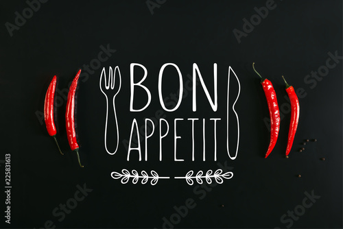 Plakaty do jadalni top-view-of-red-chili-peppers-and-peppercorns-on-black-background-with-bon-appetit-lettering-with-fork-and-knife