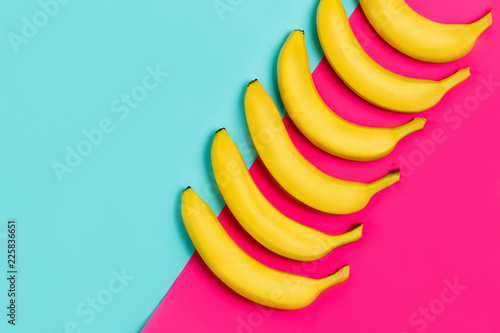 Ripe yellow bananas on a paper colorful background with copy space.