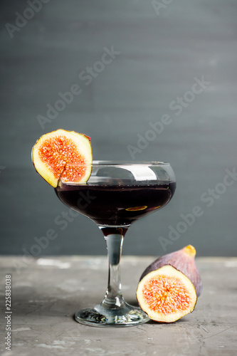 Black cocktail with figs and squid ink on the rustic background. Selective focus. Shallow depth of field.