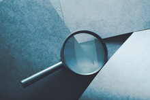 Magnifying Glass. Finding Things Or Detecting Problems Concept. Loupe On Layered Blue Paper Background.