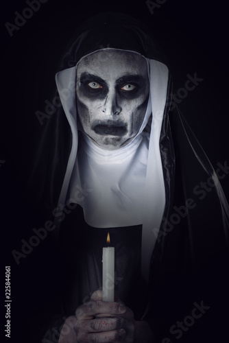 Photo frightening evil nun with a lit candle