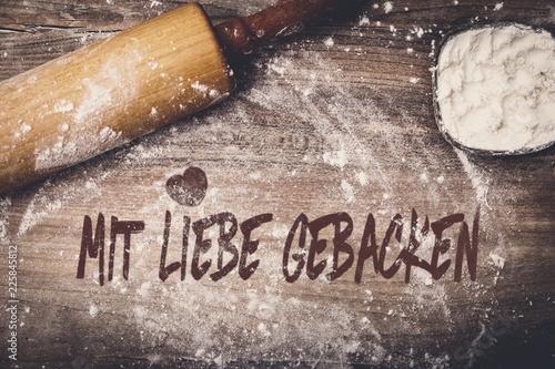 Teigrolle und Mehl auf Tisch, Text mit Liebe gebacken auf Holz