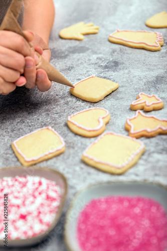 Frau beim Dekorieren von Plätzchen und Keksen mit Zuckerguss