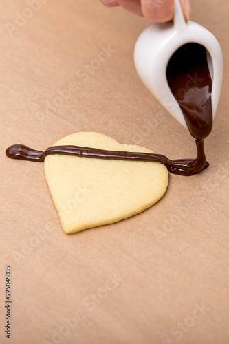 Herz Plätzchen oder Keks wird mit flüssiger Schokolade verziert
