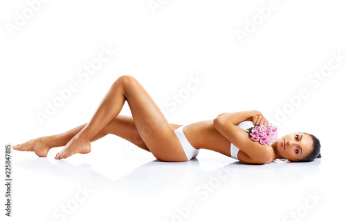 Fototapeta Young woman with beautiful long legs. Photo of tanned woman's body isolated on white background. Beauty & Skin care concept. obraz na płótnie