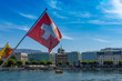Swiss flag in front of the geneve skyline, cathedrale saint-pierre geneve, yellow boat and a wonderful blue sky as seen from the pont du mont blanc bridge of Geneva, Switzerland