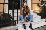 Fototapeta Na drzwi - Beautiful girl in trench coat and jeans dreamily looking in camera sitting on little stairs while spending time on cozy city street