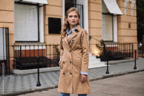 Obraz Young attractive woman in trench coat thoughtfully looking in camera while walking around cozy city street - fototapety do salonu