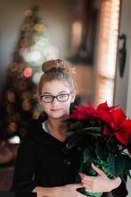 Girl Holding Christmas Poinsettia In Living Room, Portrait