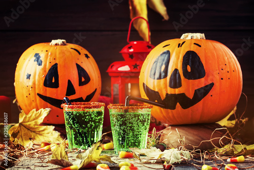 Poster Halloween composition with festive green drink and smiling drinking pumpkins, with sweet corn, straw and fallen leaves on dark background, selective focus