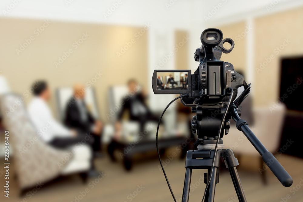 Fototapeta Video camera taking live video streaming at people talking background