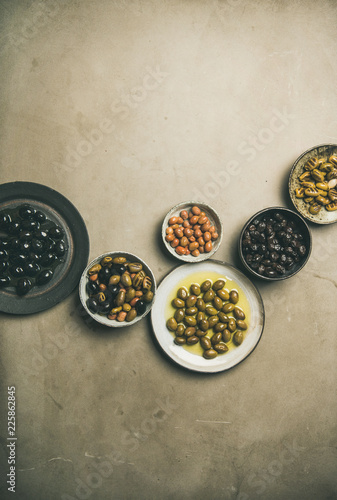 Flat-lay of various kinds of Mediterranean pickled olives in plates over grey concrete table background, top view, copy space. Mediterranean meze appetizer
