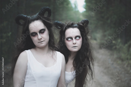 Fotografía Two twins demons with horns in forest