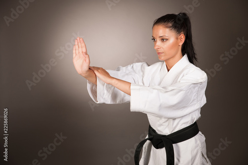 Photo  Woman in white  kimono punch hard in the air -  a karate martial art girl