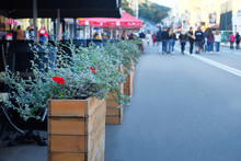 Street Wood Pot With Decorative Flowers In Outdoor Cafe On Blurred Background. Landscaping And Decoration Of City Streets.