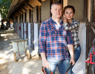 Positive family couple with belly-band standing  at stable outdoor