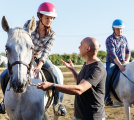 Trainer talking to female while riding horse at ranch