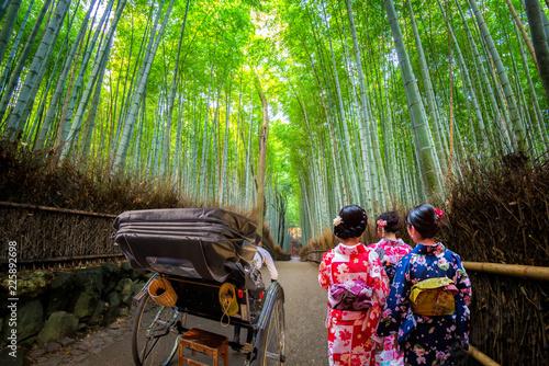 Young women wearing traditional Japanese Kimono and Rickshaw for sightseeing at Bamboo forest of Arashiyama,  Arashiyama is a district on the western outskirts of Kyoto, Japan.