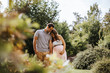 canvas print picture Schöne schwangere Frau und ihr glücklicher Partner laufen Hand in Hand durch den Park