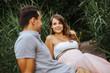 canvas print picture Schöne schwangere Frau und ihr glücklicher Partner genießen romantischen Moment auf einem Bootsanlegesteg