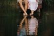 canvas print picture Spiegelung der Füße und Beine eines Liebespaars im Wasser eines Sees