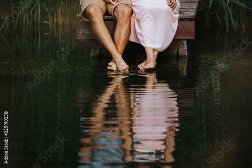 canvas print motiv - kay fochtmann : Spiegelung der Füße und Beine eines Liebespaars im Wasser eines Sees