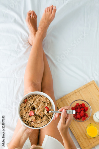 Fototapeta Attractive young woman having breakfast in the bedroom. obraz