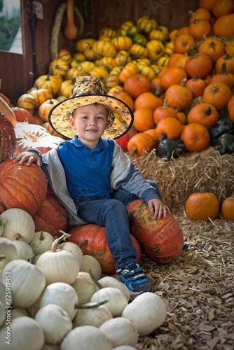 Fotografía  Little cute boy in halloween costume with pumpkins decoration on background