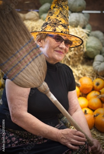 Fotografie, Obraz  Friendly witch with broom on pumpkins background.