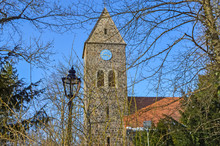 Look Through Branches To A Historic Village Church And An Old Lantern In Berlin-Lichtenrade, Germany.