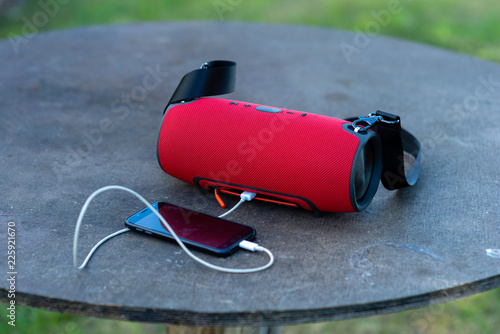 Obraz Smartphone with portable speakers is placed on a wooden table. - fototapety do salonu
