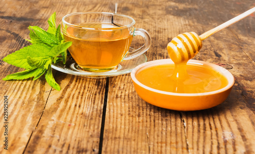 Cup of tea mint honey wooden background