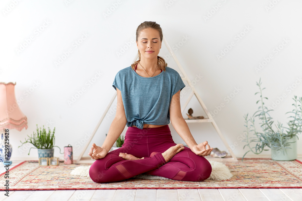 Fototapeta mindfulness, spirituality and healthy lifestyle concept - woman meditating in lotus pose at yoga studio