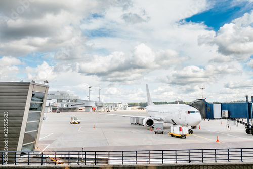 Foto White airplane on a runway docked to airport terminal