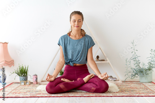 mindfulness, spirituality and healthy lifestyle concept - woman meditating in lo Fototapeta