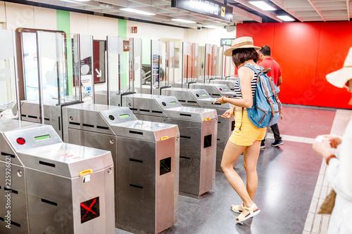 Woman enter in subway through turnstile, public railroad transport concept