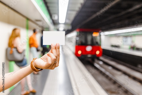 Hand holding blank metro subway ticket at the background of arriving train