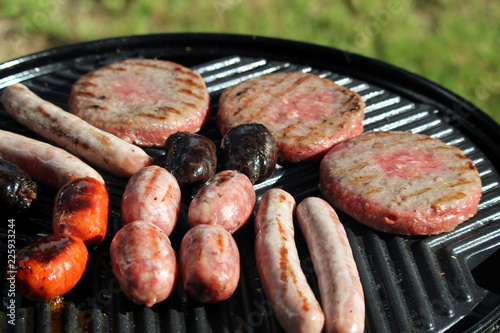 Fotografie, Obraz  Shallow focus shot of tasty assorted delicious sausages and burgers sizzling and