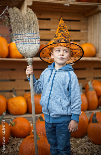 Photo  Little cute boy in halloween costume with pumpkins decoration on background